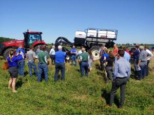 Crowd listens to speaker discussing field practices utilizing manure
