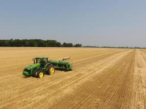 tractor pulling drill planter across harvested wheat field planting double crop beans