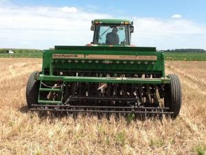 no-till drill planter being pulled by tractor in harvested wheat field