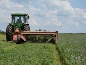 tractor pulling mower through field of hay